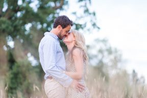 couple embrace stood in tall golden grass