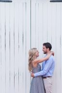 couple embrace with a white wooden building in the background