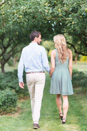 couple walking hand in hand through gardens