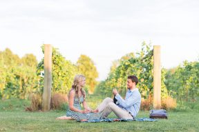 couple enjoying champagne sat on a picnic blanket at a vineyard