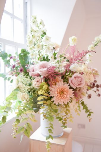 large arrngement of flowers on display with pink and peach hues