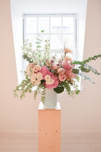 larg arrangement of flowers on display in a window with pinks and peach colours