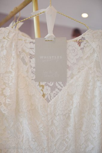 lace bridal wear by whistles with a grey label hung by a ribbon