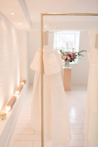 white studio space showcasing gold rails with the whistles bardot wedding dress
