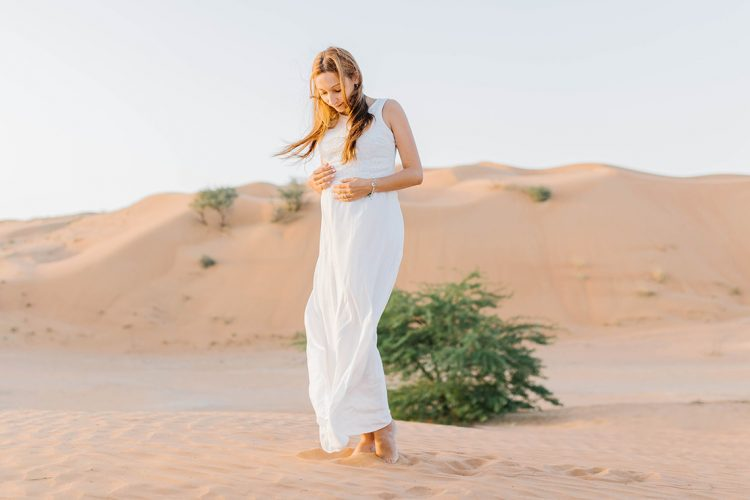 maternity portrait with a sand backdrop