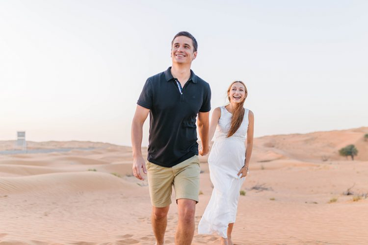 couple holding hands joyfully walking towards the camera