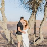 couple stood barefoot in the sand in the shade of a tree