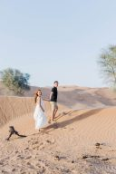 couple walk holding hands across the sand dunes