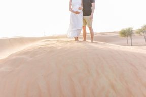 couples feet stood together on top of a sand dune