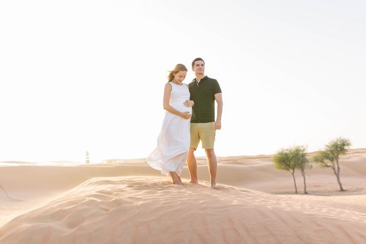 couple stood at the top of a sand dune together
