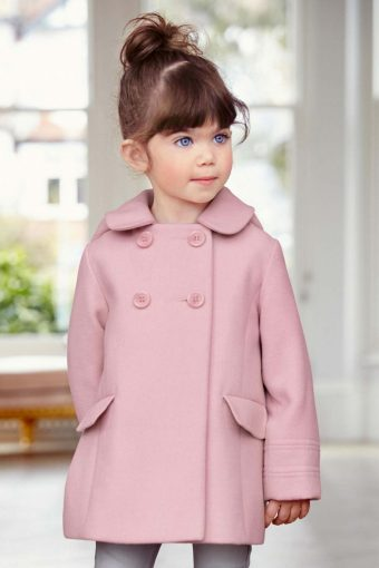 little girl wearing a pale pink double breasted coat