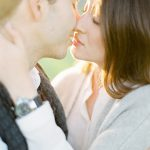couple's maternity session portrait with a sweet kiss