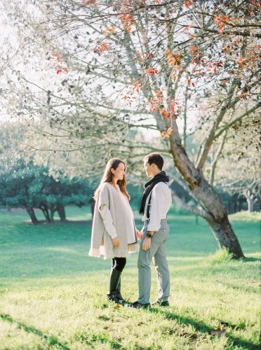 couple walk under a tree in the park