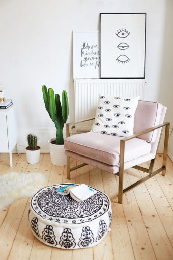 trendy living room with pink armchair and pouffe with book