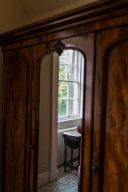 looking through the mirror which is on the antique wardrobe