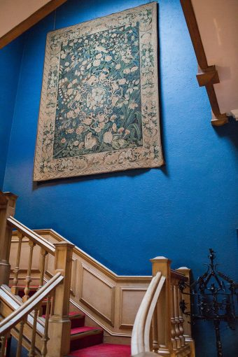 grand staircase and cobaly blue walls with a hung tapestry