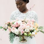 Bride holding a floral arrangement of pink flowers in an antique urn