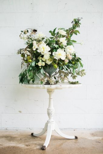 beautiful white and green floral arrangement displayed on a white wooden table