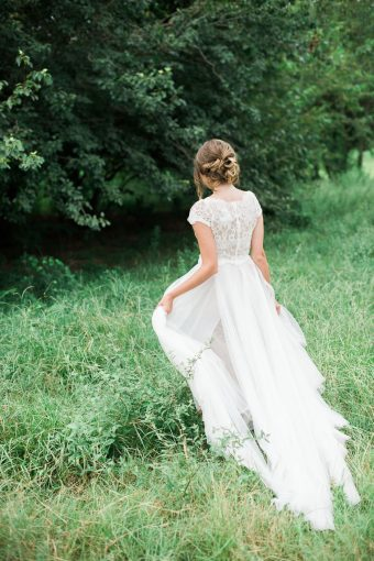 bridesmaid walking through the grass with the tulle skirt trailing romantically