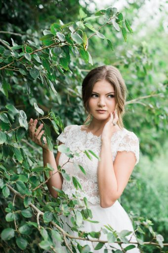 bridesmaid portrait stood by beautiful grren climbing foliage