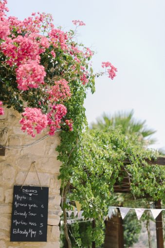 sandstone wall with a canopy of pink flowers
