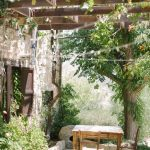 rustic country courtyard with a table and chairs under bunting