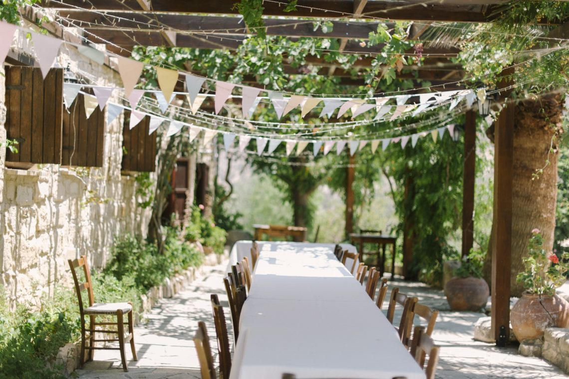 long table and chairs under a canopy of bunting