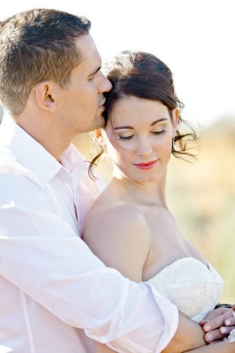 couple embrace as he kisses her lightly on the head