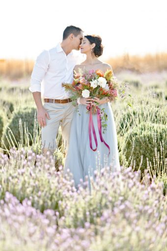 couple kiss softly amongst the beautiful field of lavender