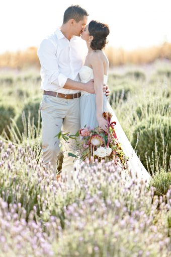 beautiful bouquet with trailing silk ribbons held by the couple stood among the lavender