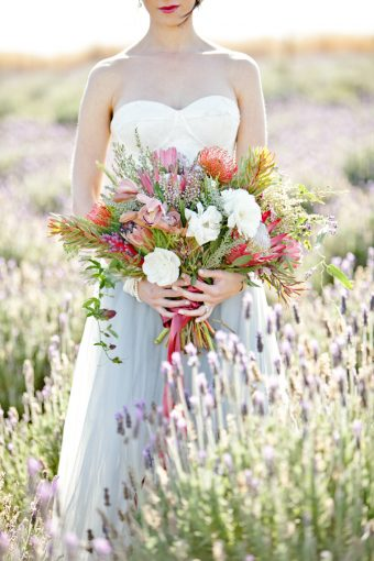 bride's beautiful bouquet held as she stands amongst the lavender field