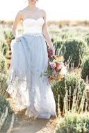 bride walking amongst the lavender holding her tulle skirt and bouquet