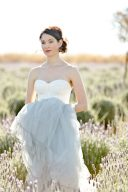 bride stood amongst the lavender holding the tulle skirt of her gown