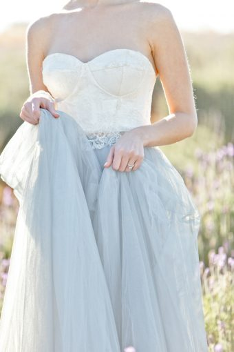 details of the bride holding her tulle skirt and showing her hands and rings