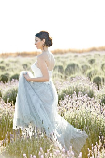 bride walking amongst the lavender holding her tulle skirt