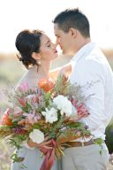 couple embrace softly whilst holding a beautiful bouquet