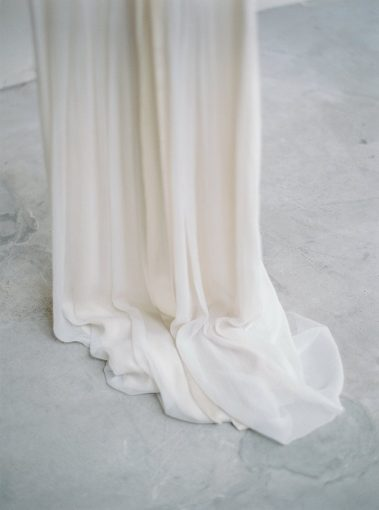 the silk wedding gown edges gather upon the floor in beautiful layers