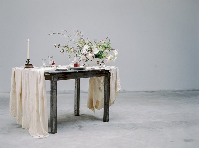 fine art wedding table setting with muslin runner magnolia flowers and taper candles