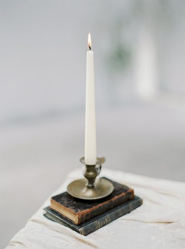 antique books with a tall tapered candle disaplayed on top