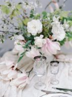 fine art wedding table setting with pink magnolia flowers and antique drinkware==