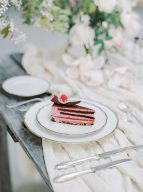 chocolate cake topped with fruit set on a beautiful wooden table with muslin runner