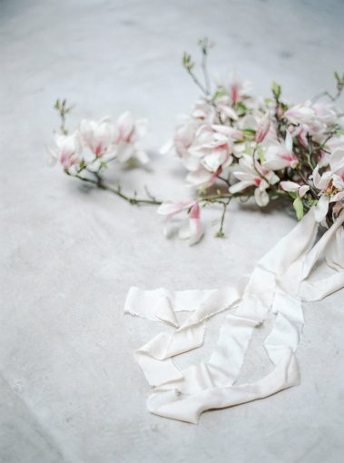 branches of pink magnolia flowers and streams of silk ribbons