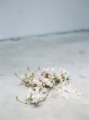 branches of pink magnolia set upon the concrete floor bound by silk ribbons which trail next to the bunch