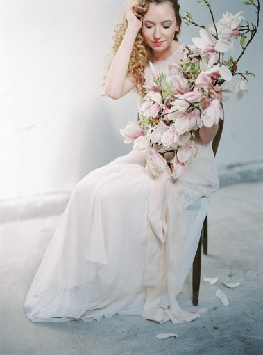 bride holding branches of pink magnolia