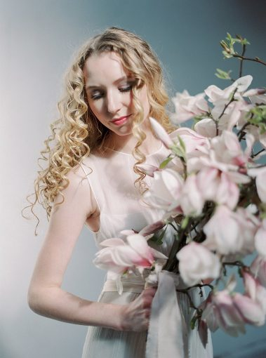 bride holding branches of pink magnolia flowers