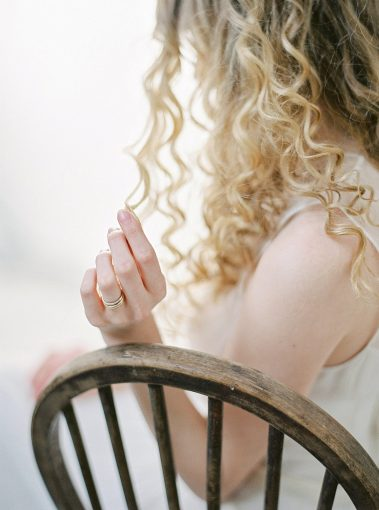 brides hand playing with her curled hair and displaying her rings