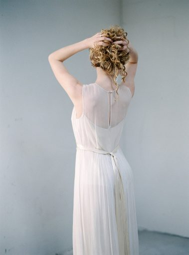 bride showing the back of her wedding dress and holding her hair