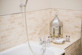beautiful bath with cream tiles and silver lantern on the side