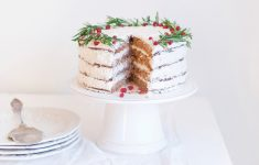 christmas cake on a cake stand with white icing and wreath style decoration around the edges