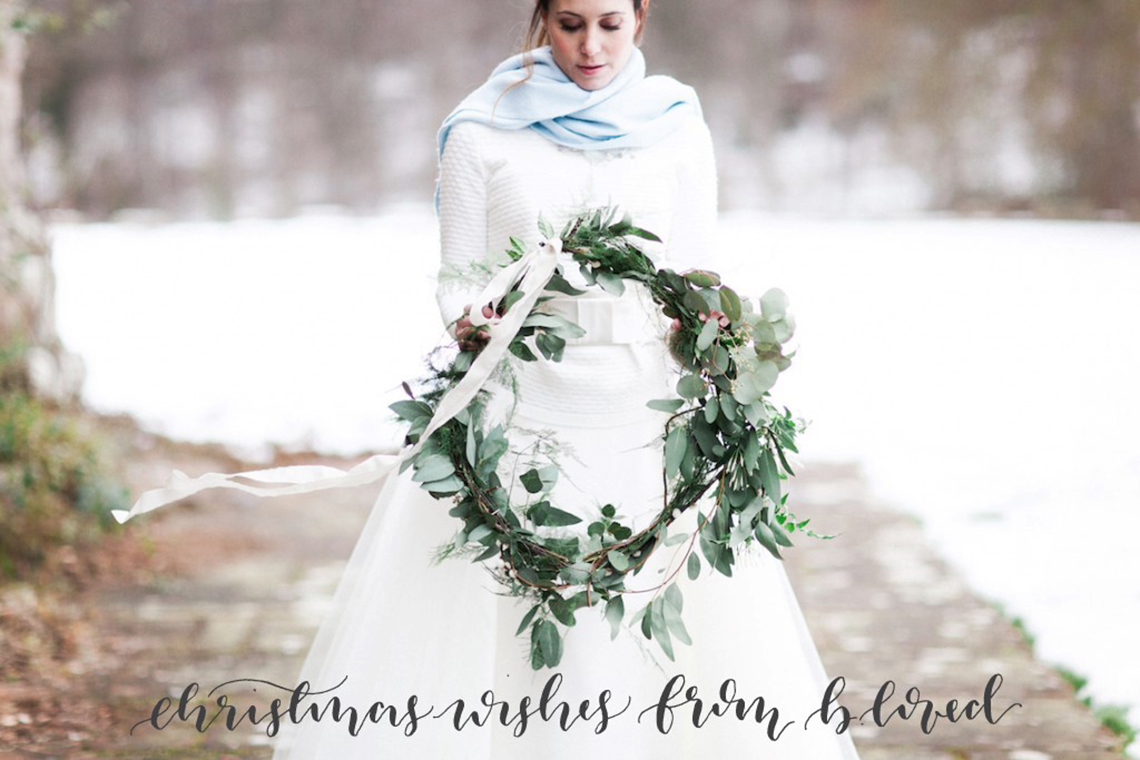Winter bride in the snow holding a wreath